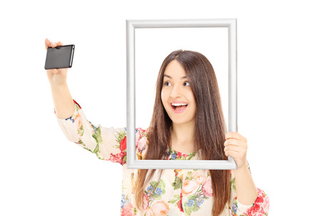Woman taking a selfie behind a picture frame isolated on white background Stock Photo