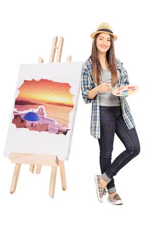 Artista femminile che si appoggia su un cavalletto con la pittura isolato su sfondo bianco