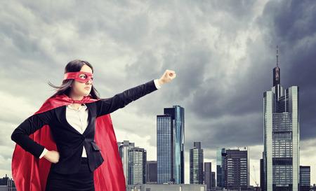 暗い街前の女性のスーパー ヒーローの地位 写真素材