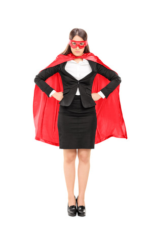 Full length portrait of a woman in superhero costume standing proudly isolated on white background