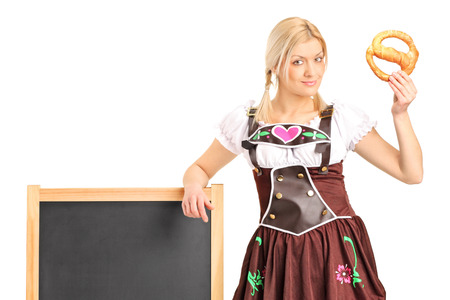 Young german girl in a traditional costume holding a pretzel isolated on white background photo