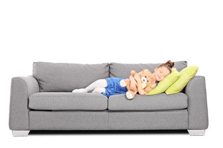 enfant qui dort: Fille embrassant un ours en peluche et dormir sur le canapé isolé sur fond blanc