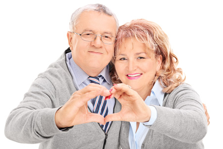 Mature couple making heart with their hands isolated on white background photo
