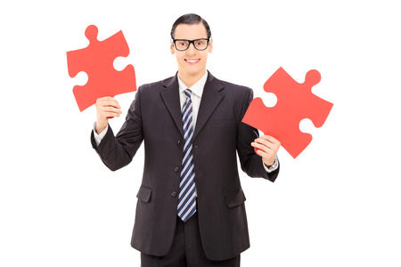 Young businessman holding two pieces of puzzle isolated on white background photo