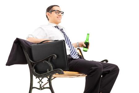 chilling out: Empresario relajarse con una cerveza sentado en un banco aislado en el fondo blanco