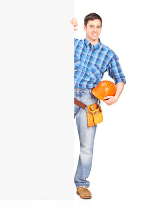 Male construction worker standing behind blank panel isolated on white background photo