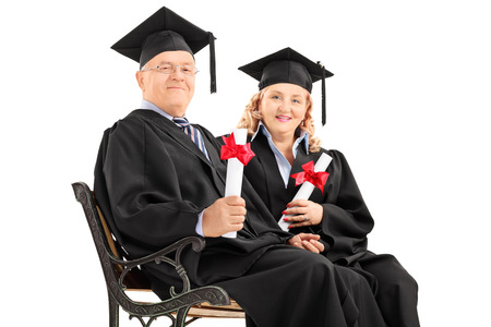 mature people: Mature people posing with diplomas seated on a bench isolated on white background