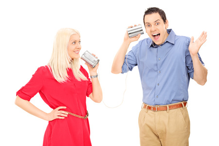 Young couple having fun with a tin can phone isolated on white background photo