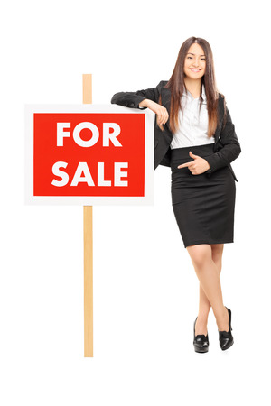 Woman pointing towards a for sale sign isolated on white background photo