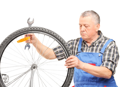 Mature bicycle mechanic looking at a wheel isolated on white background photo
