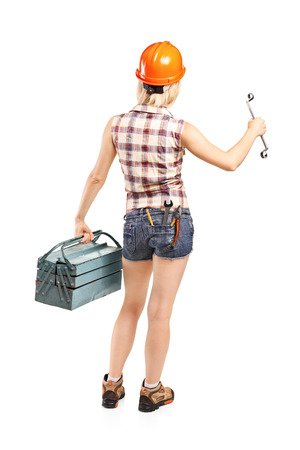 Female mechanic holding a toolbox isolated on white background, rear view photo