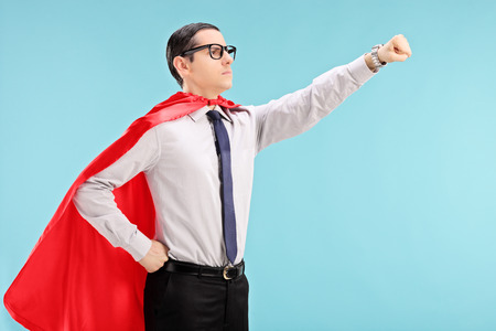 proud: Proud super hero with gripped fist on blue background Stock Photo