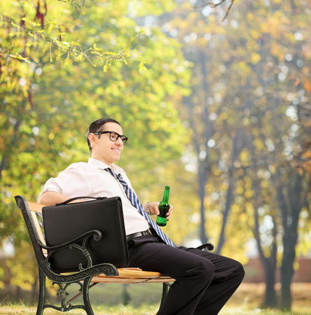 Businessman taking a break in park with a beer shot with tilt and shift lens Stock Photo