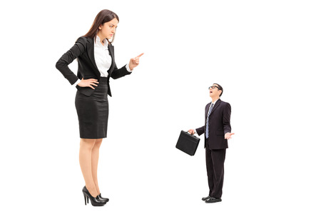 Giant woman threatening a tiny businessman isolated on white background Stock Photo