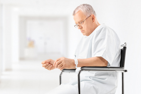 devastated: Worried mature patient sitting in a wheelchair in a hospital corridor