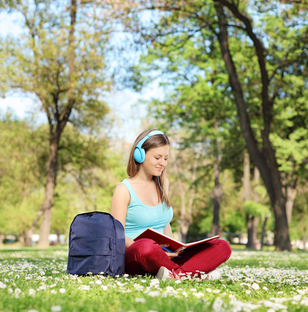 Woman with headphones studying in park seated on the grass shot with tilt and shift lens photo