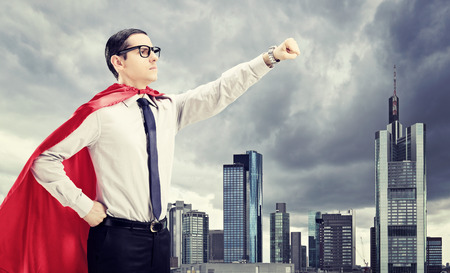 20s adult: Superhero standing In front of a dark city with his fist in the air