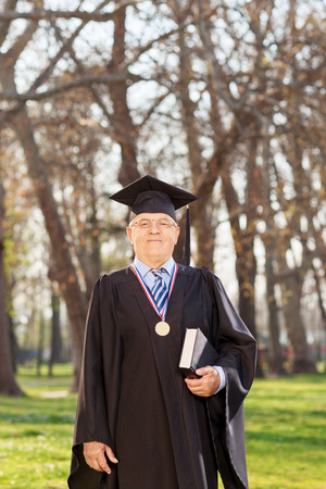 dean: College dean in graduation gown holding a book in a park