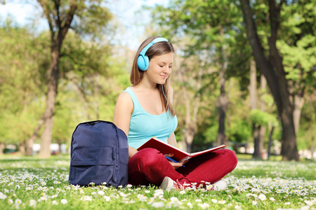 Female student reading a book in park seated on green grass photo
