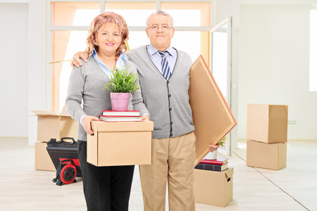 male senior adult: Husband and wife holding moving boxes and posing in their new apartment