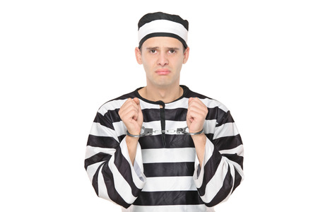 Sad male prisoner with handcuffs isolated on white background