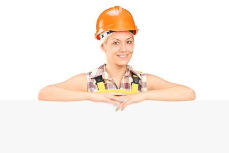 Female construction worker posing behind blank panel isolated on white background photo