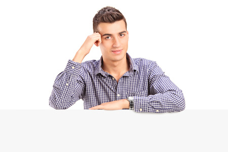 Man posing behind a blank panel isolated on white background photo
