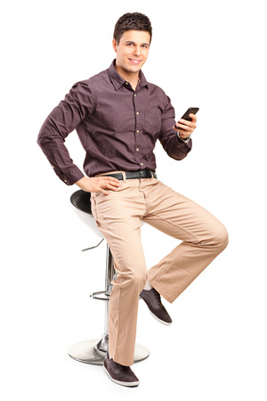 man in chair: Man sitting on chair and holding cell phone isolated on white background Stock Photo