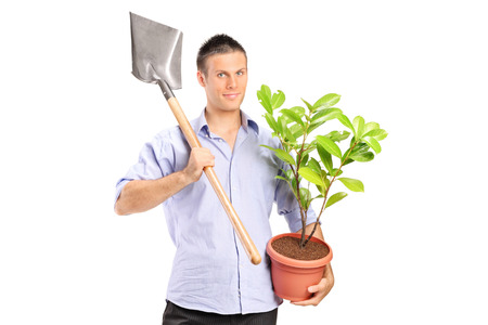 Man holding a shovel and a plant isolated against white background photo