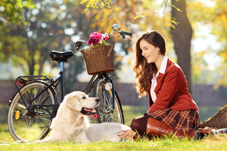 green clothes: Pretty female sitting down with her dog in a park