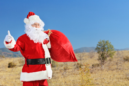 Santa holding a bag of presents and hitchhiking outdoor photo
