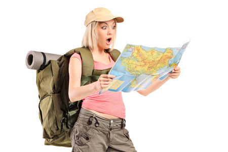 Surprised female hiker looking at a map isolated against white background photo
