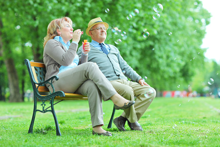 nonchalant: Elderly couple blowing bubbles in park seated on bench
