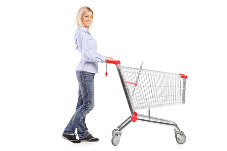 woman shopping cart: Woman pushing a shopping cart isolated on white background