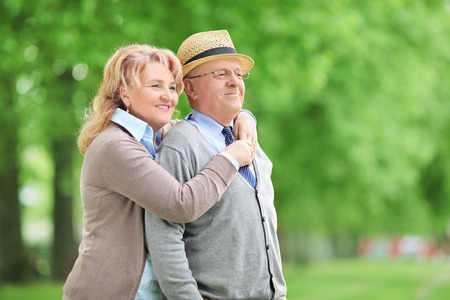 Carefree elderly couple hugging outdoors photo