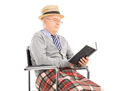 hombre sentado: Senior hombre leyendo un libro sentado en sillón de ruedas aislado en el fondo blanco