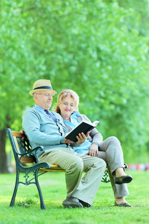Mature couple reading a book seated on bench in park  photo