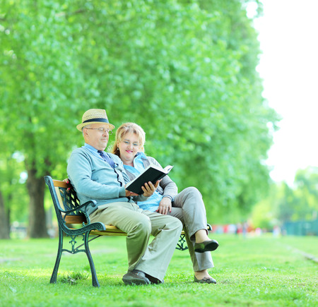 Elderly couple reading a book seated on a bench in park shot with tilt and shift lens  photo