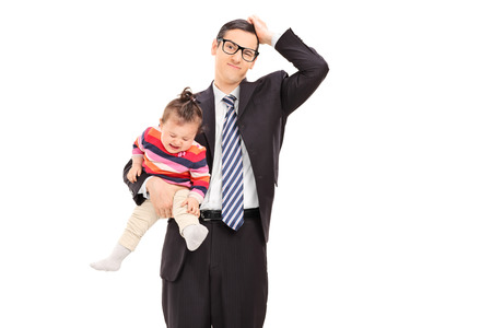 Confused businessman holding a crying baby isolated on white background photo
