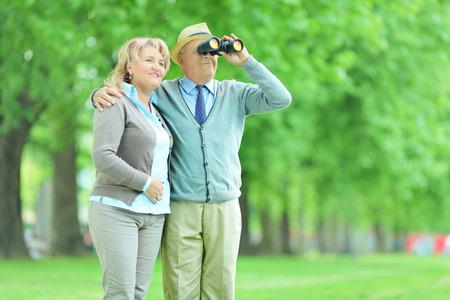 Senior couple looking through binoculars outdoors photo