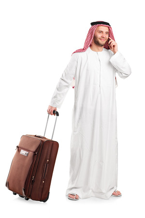 sheik: Full length portrait of an Arabic sheik talking on phone and carrying a luggage isolated on white background Stock Photo