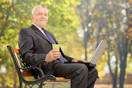 laptop outside: Mature businessman taking a break seated on bench in park
