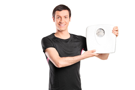 Young man holding a weight scale isolated on white background photo