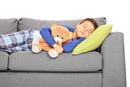Little boy taking a nap on a couch isolated on white background photo