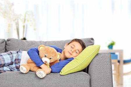 Little kid sleeping on sofa with a teddy bear indoors photo