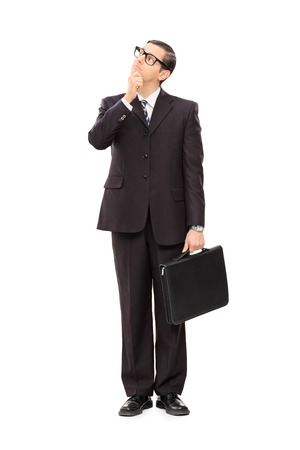Full length portrait of a young businessman deep in thought isolated on white background photo