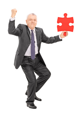 Joyful mature businessman holding a piece of puzzle isolated on white background photo