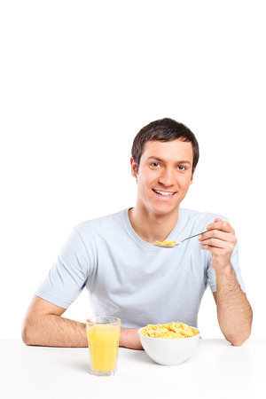 Young man eating cereal and drinking orange juice isolated on white background photo
