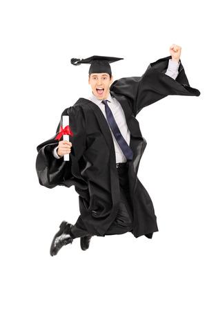Estudiante graduado masculino saltando de alegría aislado sobre fondo blanco