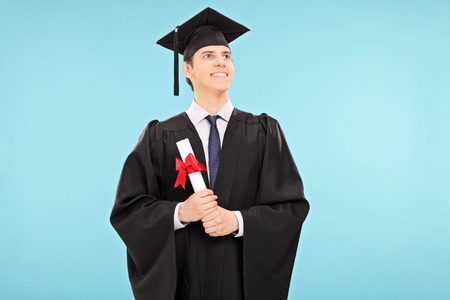 relieved: Proud male graduate student holding a diploma on blue background